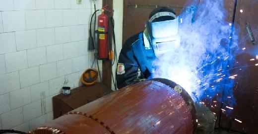welder works in a factory in the helmet.