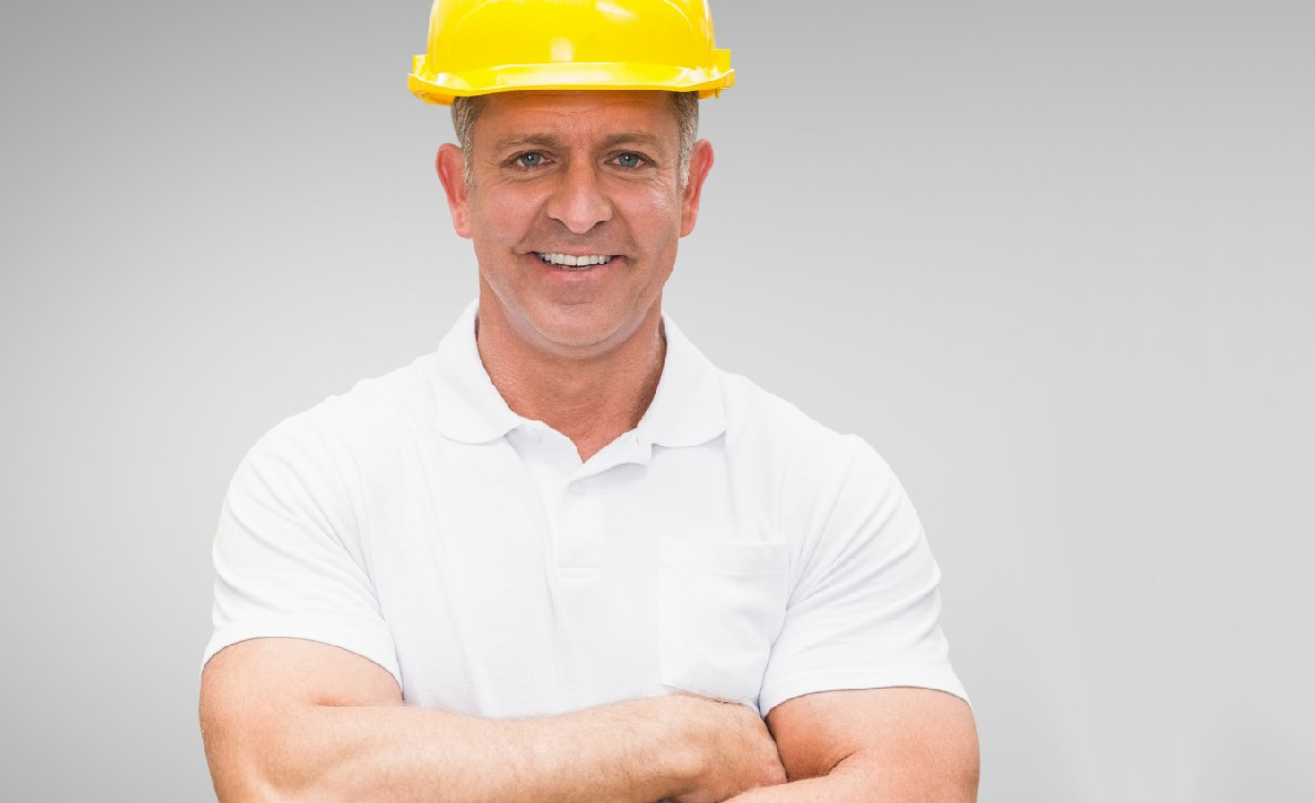 Portrait of worker standing with arms crossed against grey background